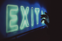 Anonymous person near neon exit sign Free Stock Photo