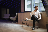 Confident businessman sitting on armchair near window in modern spacious workspace Free Stock Photo