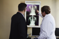 Doctor Pointing X ray Result Beside Man Wearing Black Suit Free Stock Photo