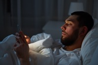 Man with smartphone in bed at night P3U9SAN