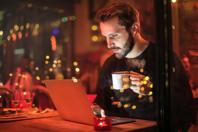Man Holding Mug in Front of Laptop Free Stock Photo