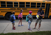 Students are given bus stickers after getting off the bus at Northeast Elementary School in Jackson on Tuesday morning, Aug. 25, 2020. Jackson Public Schools buses will soon begin delivering WiFi into neighborhoods where district families can't afford internet access.J. Scott Park | MLive.com