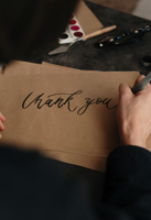 Person Writing on Brown Printer Paper Free Stock Photo