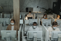 PEople working at computers with masks.