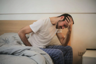 man getting up from bed holding his head.