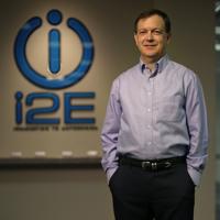 Scott Meacham in front of i2E's logo