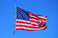 US Flag flowing in the breeze against a blue sky