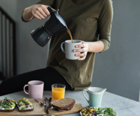 Woman in Green Top Pouring Coffee in a White Mug Free Stock Photo