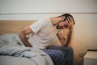 Young man in sleepwear suffering from headache in morning Free Stock Photo